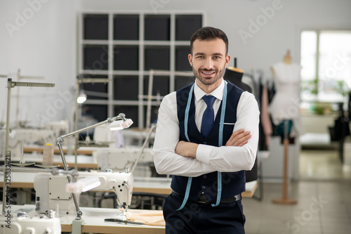 Fototapety, obrazy: Male tailor standing with folded hands, smiling