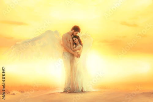 Gentle embrace hug heaven angels with white wings. Sexy Man kiss female head with long hair pressed against strong male chest Model fantastic costume pastel colors. Backdrop bright sunny sunset desert