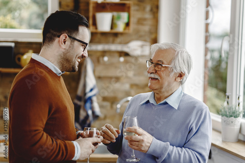 Happy mature man talking with his adult while drinking wine in the kitchen Fototapete