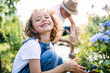 Leinwandbild Motiv Small girl with senior grandfather in the backyard garden, gardening.