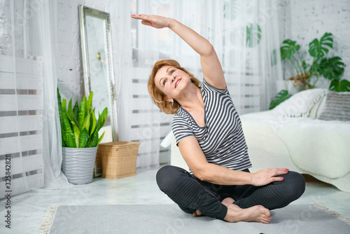 Slika na platnu Senior woman exercising while sitting in lotus position