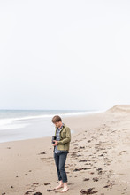Young Man Standing On Beach Ta...