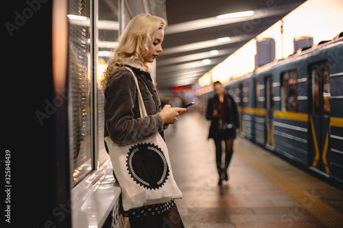 Young woman using smartphone while waiting for subway train on platform - 325848439