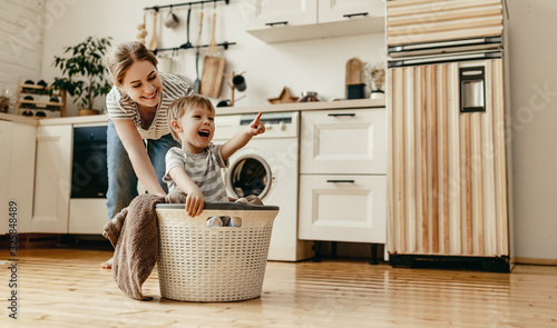 Obraz na plátně Happy family mother housewife and child   in laundry with washing machine