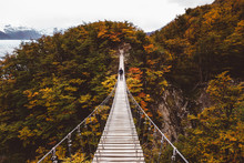 Man Standing On Suspension Bridge In Mountains