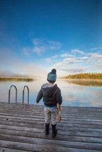 Young Boy Standing On Wooden Dock At The Lake.