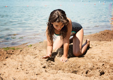 Young Girl In Swimsuit On Shore Of Lake Looking At A Monarch Butterfly