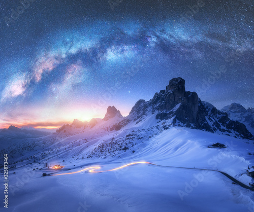 Milky Way over snowy mountains and blurred car headlights on the winding road at night in winter. Beautiful landscape with starry sky, snow covered rocks, house, roadway at sunset. Space and galaxy Wall mural