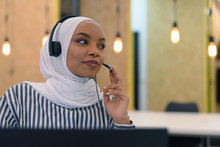 Female Customer Service Representative Answer Client's Questions In A Headset. Multi-Ethnic Team Of Specialists. Happy African Muslim Woman In Call Center.