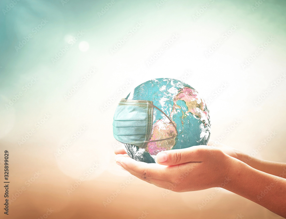 Fototapeta COVID-19 prevention concept: Human hands holding earth globe with medical disposable face mask. Elements of this image furnished by NASA