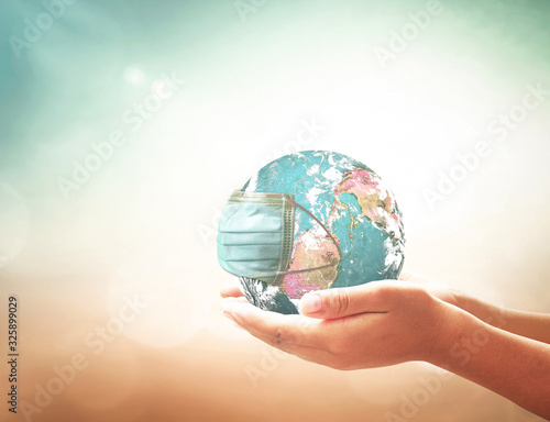 Fotomural COVID-19 prevention concept: Human hands holding earth globe with medical disposable face mask
