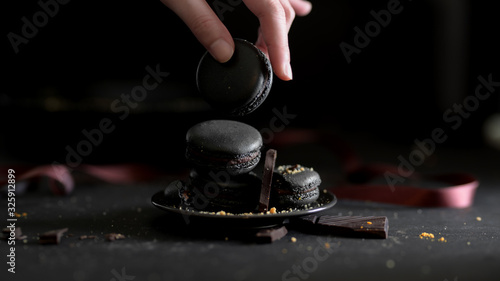 Cropped shot  of a girl picking dark chocolate macaron from black plate Poster Mural XXL