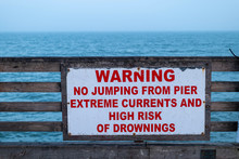 Sign On Pier At The Ocean. WARNING NO JUMPING FROM PIER EXTREME CURRENTS AND HIGH RISK OF DROWNINGS