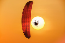 Colorful Powered Paraglider In The Sun And Against The Orange Sky