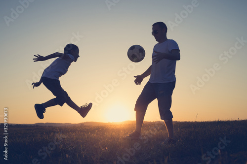 Obraz Father and young little boy playing in the field  with soccer ball. - fototapety do salonu