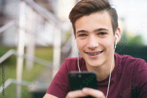 Fototapeta Close-up portrait of a smiling young man with a smartphone, in the street.  Happy teenage boy is using mobile phone, outdoors. Cheerful teenager spends time in social networks using cell phone. obraz