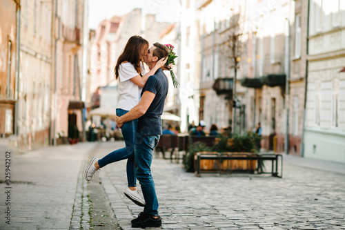 Photographie Smiling Young couple with a bouquet of flowers in love hug each other in love outdoors