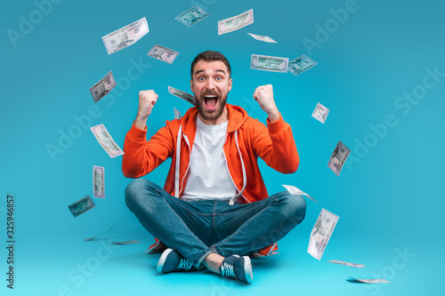 Fototapeta Young attractive bearded man celebrating victory after betting at bookmaker's website obraz