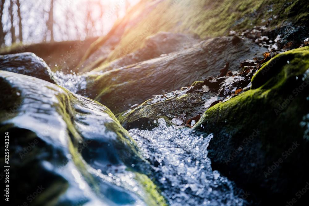 Fototapeta water flowing over rocks