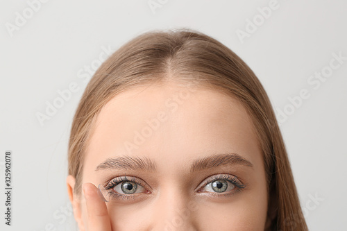 Young woman with contact lens on grey background Canvas Print