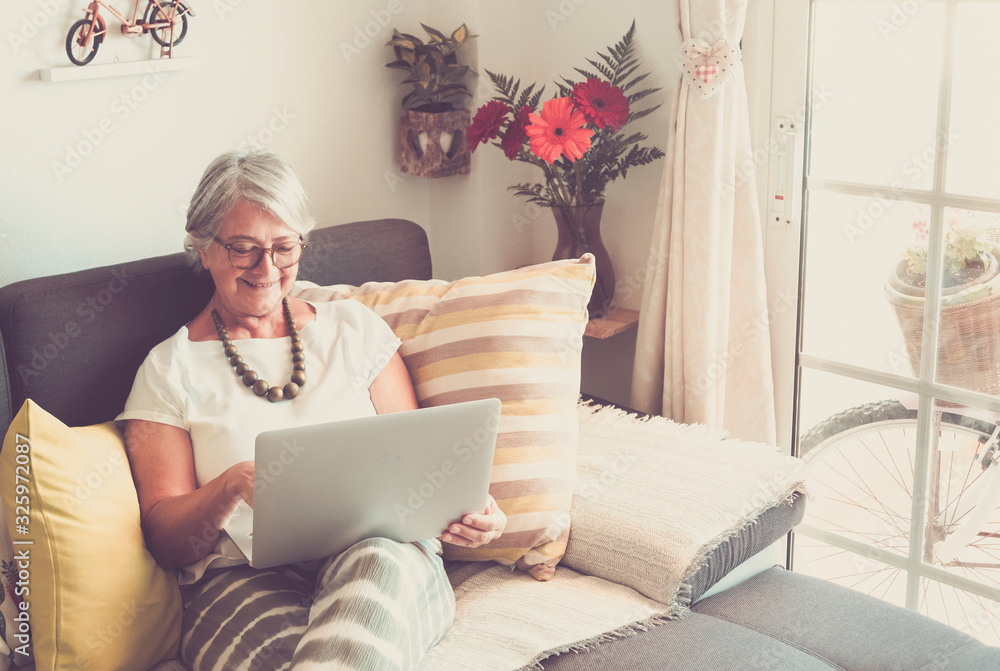 Fototapeta Attractive senior woman relaxing on the sofa surfing the net with laptop. One real people. A vintage bicycle out of the window. Happy with technology