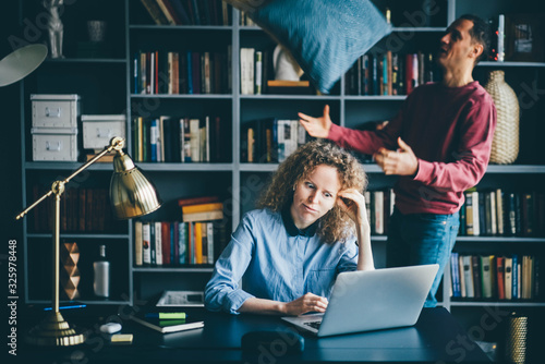 Woman working hard whit laptop while man having fun at modern home office Canvas Print