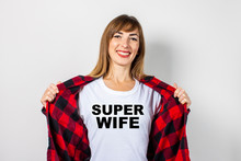 Young Woman With A Smile In A Red Shirt And White T-shirt On A White Background. Super Wife Text Has Been Added To The Shirt. Concept For Text, Logo, Shock, Surprise. Banner