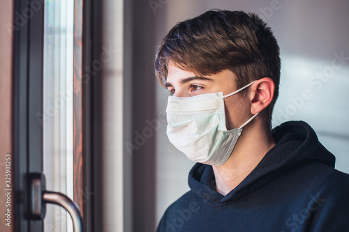 Obraz young boy with protective mask - pandemic infection fear concept - quarantine at home - stay at home - fototapety do salonu