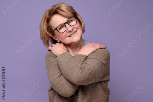 Fotografía Positive senior caucasian woman in glasses smiling, keeping arms around herself