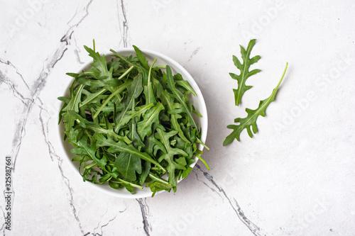 Photo Bowl of fresh green arugula leaves