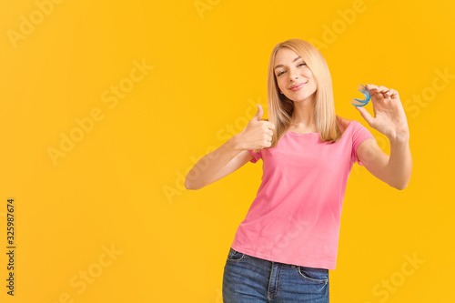 Leinwand Poster Young woman with dental braces and mouth protector showing thumb-up gesture on c