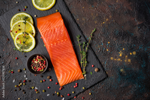 Fototapeta Piece of red fish fillet with spices on black slate board with lemon. obraz