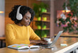 Young woman having online training, using laptop and wireless headset