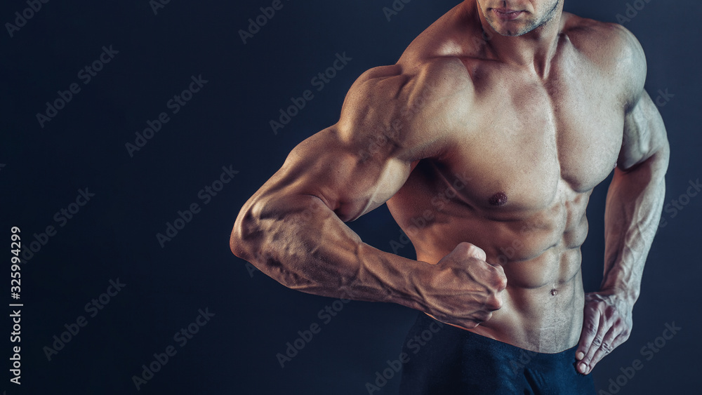 Fototapeta Unrecognizable Strong Athletic Sexy Muscular Man Poising , Showing biceps and delts on Black Background.