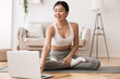 Sport application. Asian girl practicing yoga and using laptop