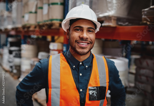 Smiling warehouse manager in safety vest and hard hat Fototapete