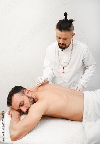 Doctor doing an acupuncture for a patient to treat chronic back pain Canvas Print