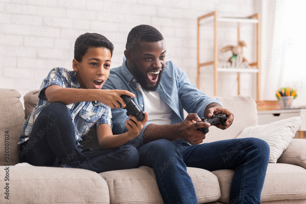Fototapeta Cheerful Black Father And Son Competing In Video Games At Home