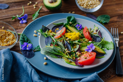 Fototapeta Fresh healthy salad with edible flowers, green, avocado, tomato and pine nuts obraz