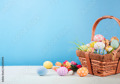 Fotografiet Happy easter, Easter painted eggs in the basket on wooden rustic table for your decoration in holiday