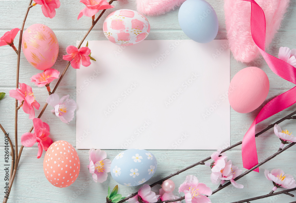 Fototapeta Happy easter, mockup paper card and easter painted eggs in nest on wooden table. Top view with copy space.