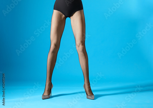 Obraz Woman wearing black tights and stylish shoes on blue background, closeup of legs - fototapety do salonu