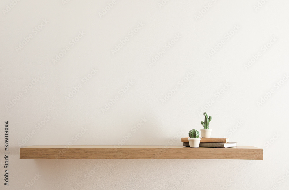 Fototapeta Wooden shelf with books and decorative cactuses on light wall