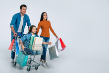 Lovely Day. Young Father And Mother Are Excited While Being On Their Shopping Spree Together With Their Beautiful Little Daughter, Who Is Sitting In A Shopping Cart With Lots Of Paper Bags.