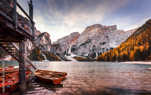 Wall mural - scenic image of Fairy tale lake in Alps. Wonderful Dolomites Alps. Famous Braies lake, Lago di Braies during sunset. Amazing nature landscape with calm lake, autumn forest and rock mount under sunlit