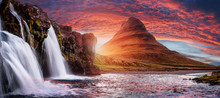 Mount Kirkjufell With Dramatic Sky In Iceland.Summer Sunset Over The Famous Kirkjufellsfoss Waterfall With Kirkjufell Mountain In The Background In Iceland. Long Exposure. Picturesque Epic Scenery