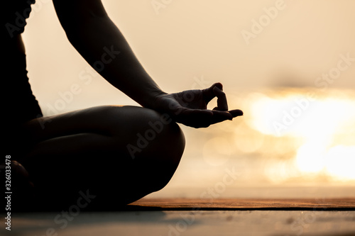 Silhouette Close up hand of woman practice yoga meditation lotus pose on the beach in thailand,Feeling so comfortable and relax in holiday with golden light,Healthy Concept,warm tone