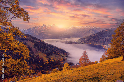 Wall mural - Incredible Nature Landscape., foggy morning during sunrise at Alpine lake in autumn. Colorful Sky over the Zeller Lake in Zell am See, Salzburger Land, Austria. Creative image. Natural Background