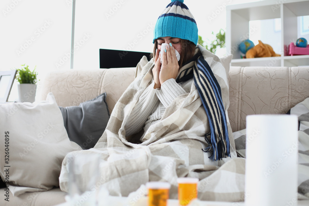 Fototapeta Portrait of sad ill woman blowing nose in paper napkin. Diseased person on sick leave. Female taking medication. Seasonal sickness and treatment concept