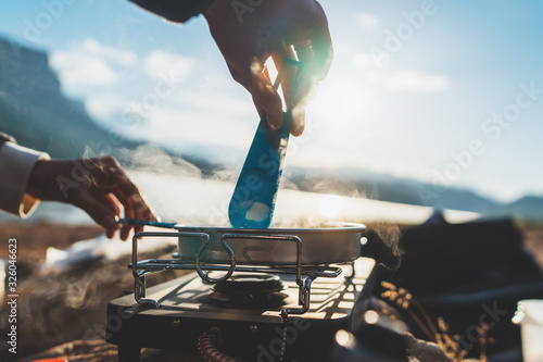 Leinwand Poster person cooking food in nature camping outdoor, cooker prepare breakfast picnic o